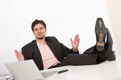 Young businessman gesturing at office. Having legs up Stock Photo