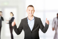 Young businessman gesturing ok sign. Young smiling businessman gesturing thumbs up Royalty Free Stock Photography