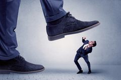 Young businessman getting crushed. Young handsome businessman getting crushed by a big formal shoe stock photo