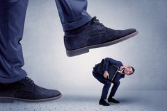 Young businessman getting crushed. Young handsome businessman getting crushed by a big formal shoe Stock Images