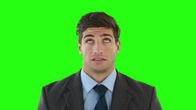 Young businessman getting a headache. Against green background stock video footage