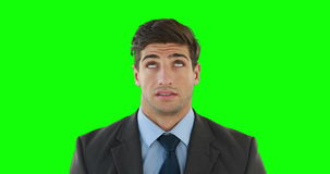 Young businessman getting a headache. Against green background stock video