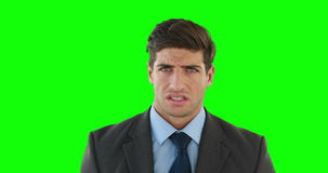 Young businessman getting a headache. Against green background stock footage