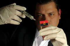 Young businessman gives a financial injection to Angolan flag Stock Photos
