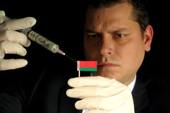 Young businessman gives a financial injection to Belarusian flag Royalty Free Stock Photography