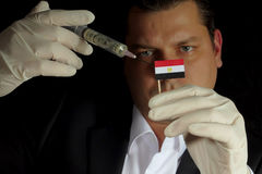 Young businessman gives a financial injection to Egyptian flag i stock images