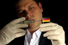 Young businessman gives a financial injection to German flag iso Stock Images
