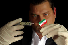 Young businessman gives a financial injection to Iranian flag. Isolated on black background Stock Photos