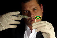Young businessman gives a financial injection to Jamaican flag. Isolated on black background stock image
