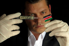 Young businessman gives a financial injection to Kenyan flag isolated on black background Stock Photography
