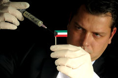 Young businessman gives a financial injection to Kuwaiti flag isolated on black background Stock Photo