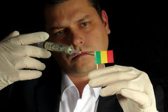 Young businessman gives a financial injection to Malian flag isolated on black background stock photography