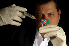 Young businessman gives a financial injection to Namibian flag i Stock Photography