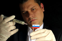 Young businessman gives a financial injection to Slovenian flag Stock Image