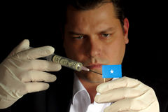 Young businessman gives a financial injection to Somalian flag i. Solated on black background Stock Photo
