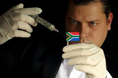 Young businessman gives a financial injection to South African flag. Isolated on black background royalty free stock image
