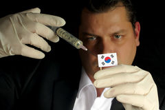 Young businessman gives a financial injection to South Korean flag stock photo