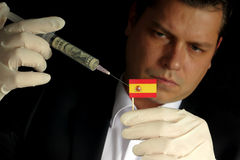Young businessman gives a financial injection to Spanish flag is. Olated on black background Royalty Free Stock Photo