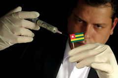 Young businessman gives a financial injection to Togolese flag i stock photo
