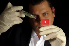 Young businessman gives a financial injection to Tunisian flag i stock image