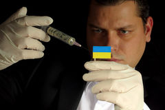 Young businessman gives a financial injection to Ukrainian flag Stock Photos