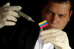 Young businessman gives a financial injection to Venezuelan flag Royalty Free Stock Photos