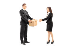Young businessman giving a box to his female colleague. Full length portrait of a young businessman giving a box to his female colleague, isolated on white stock image