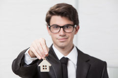Young businessman giving house keys Royalty Free Stock Images
