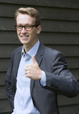 Young businessman giving thumbs up Stock Photo
