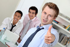 Young businessman giving thumbs-up Stock Photos
