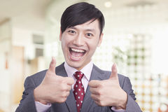 Young businessman giving the thumbs up sign, portrait Stock Photo