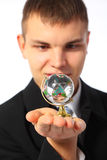 Young businessman with glass globe on palm Stock Photos