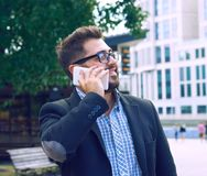 Young businessman in glasses with a beard talking on the phone walking down the street. Young smiling businessman in glasses with a beard talking on the phone royalty free stock images