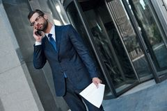 A young businessman with glasses and a beard is upset by a failed deal. In his hands he holds a contract and speaks on the phone royalty free stock photos
