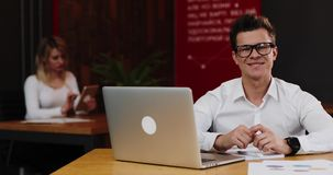 Young businessman in glasses with laptop computer and paper working in office. Business, people, paperwork and stock video footage
