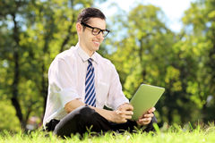 Young businessman with glasses sitting on a grass and working on Stock Photography