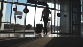 Young businessman going to the airport with his luggage and talking on phone. Man walking with suitcase. Guy goes stock footage