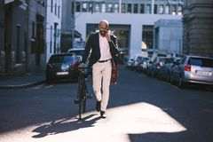 Young businessman going to work with his bicycle stock images