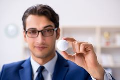The young businessman with golf ball working in office royalty free stock images