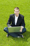 Young businessman on the grass with his laptop. Young businessman sitting on the grass with a laptop, smiling Royalty Free Stock Images