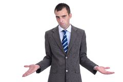 Young  businessman in a gray suit rejecting the responsibility,. Young  businessman in a gray suit rejecting the responsibility with a shrug and tight lips Stock Photo