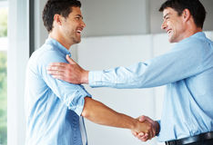 Young businessman greeting a colleague at office Royalty Free Stock Photography