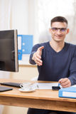 Young businessman greeting someone at workplace Stock Photos
