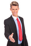 Young businessman greets you. Young businessman in a suit holds out his hand for a handshake and welcome Royalty Free Stock Image