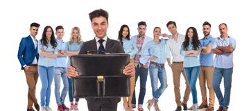 Young businessman group leader offering you his suitcase. While his casual team is standing behind on white background stock image