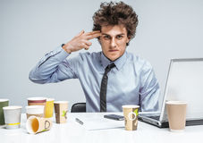 Young businessman with gun wants to commit suicide. / modern office man at working place, depression and crisis concept stock photography