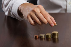Young businessman hand holding a coin with row stacks Stock Photography