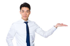 Young businessman with hand showing something Stock Photography