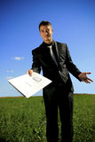 Young businessman handing a folder. A folder presented to you by a business person in black suit Royalty Free Stock Photos