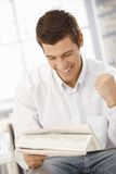 Young businessman happy about news. Reading in papers, raising fist, laughing Stock Image